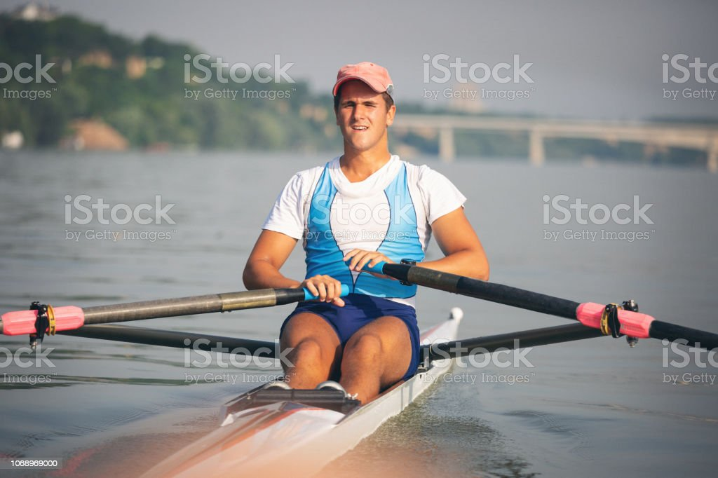 Outdoor shoots of rowing team exercising on the Danube river. Shallow...