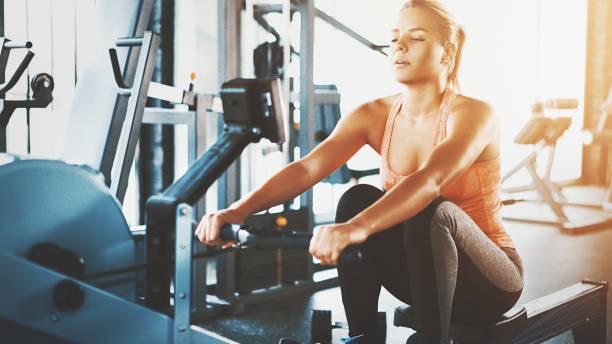 Entrenamiento de remo en el gimnasio. - foto de stock