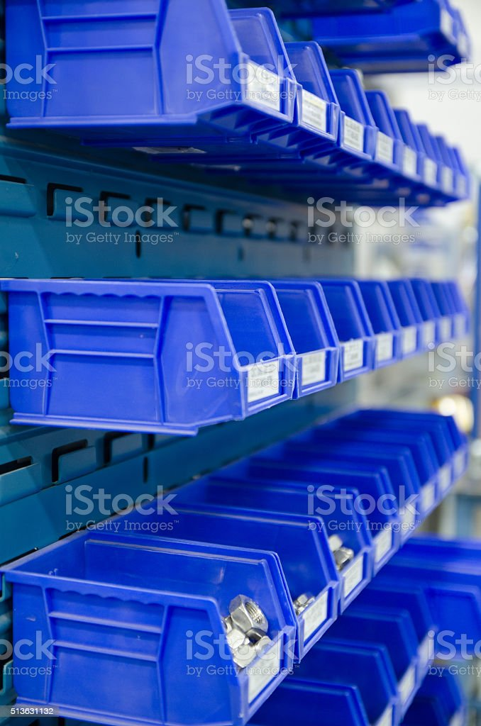 Rows blue plastic storage bins containing screws, bolts and nuts. stock photo