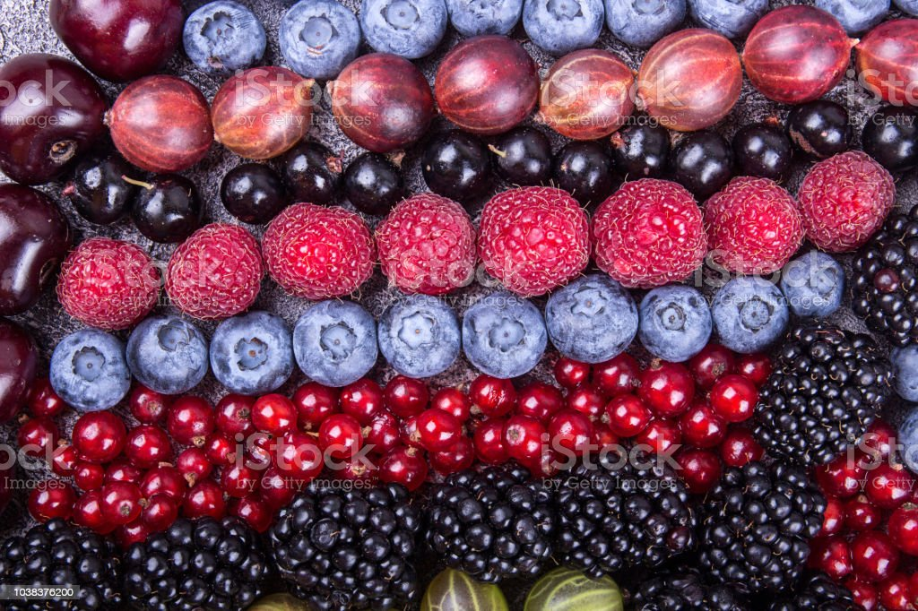 Rows of assorted fruits and berries: sweet cherry, bluberries, raspberries, red and black currant, blackberries. Helthy eating food concept. stock photo