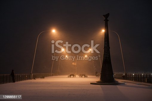 City during bad weather: snowfall and blizzard. General view of pier covered with snow. Several groups of wooden park benches and tables in the frame. Lights from the lights around the edges illuminate the entire photo. Due to the strong wind and long exposure, snowflakes leave traces in the photo. The surface is completely covered with snow. The opposite bank is not visible, instead it is a solid black and blue haze. Snow continues to fall and snowflakes are visible flying in the air. An American flag flies in the distance. The photo looks very atmospheric and mythical. The lanterns are in a row one after the other on both sides of the frame. American Veterans Memorial Pier is on the right side of the photo. Night. December 16, 2020. NYC. Brooklyn. Bay Ridge. New York. USA
