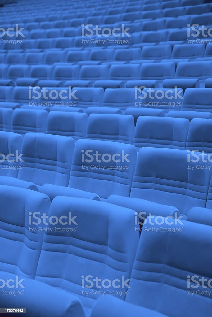 Rows of blue arm-chairs in empty hall stock photo