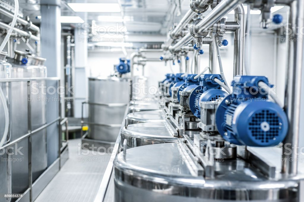 Rows of blue electric motors on tanks for mixing liquids stock photo
