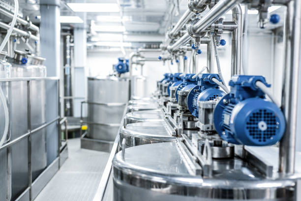 rows of blue electric motors on tanks for mixing liquids - brewery tanks stock pictures, royalty-free photos & images