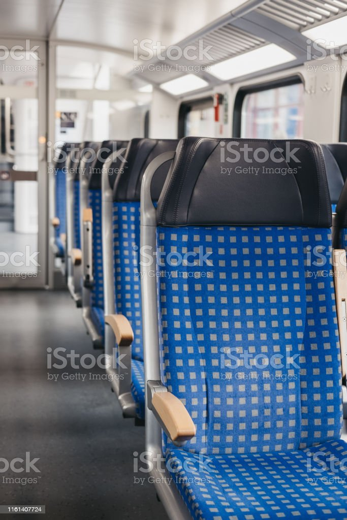 Rows of blue fabric seats with leather headrests on one side of an...