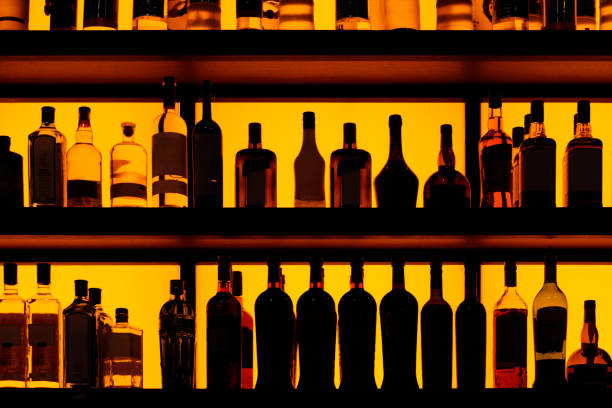 Rows of bottles sitting on shelf in a bar stock photo