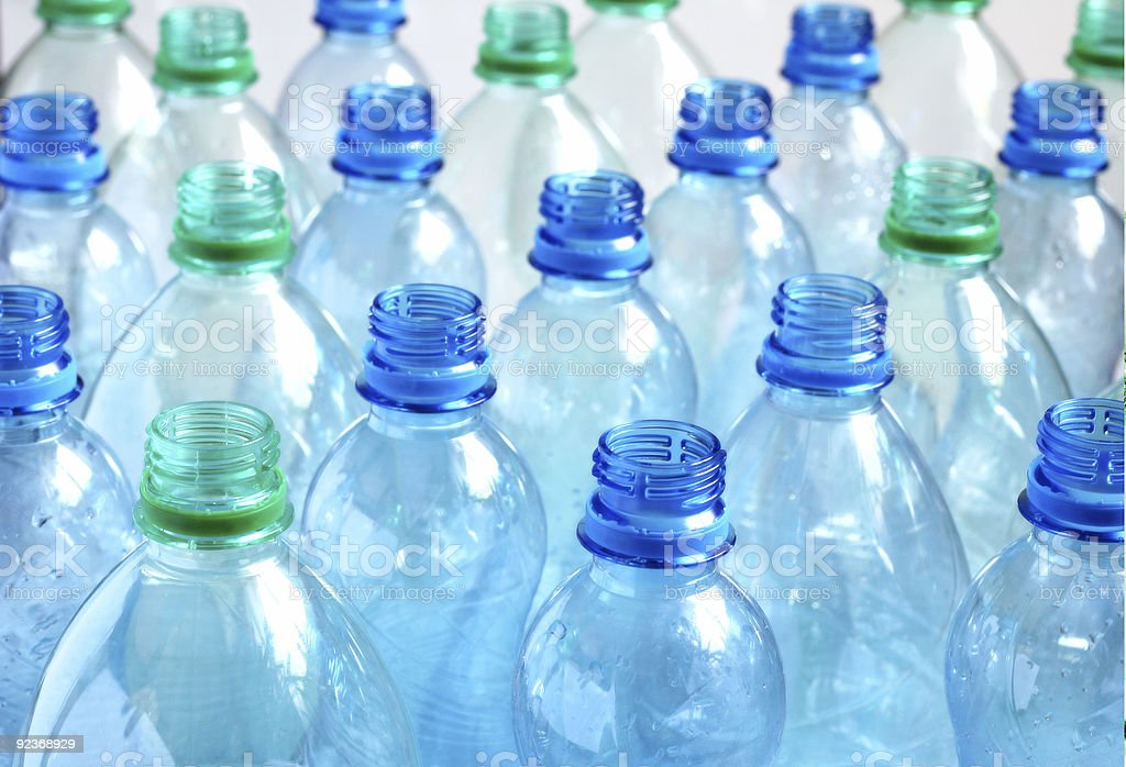 Rows of capless empty water bottles with blue and green tops stock photo