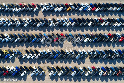 Aerial photograph of rows of cars parked in a large parking lot.