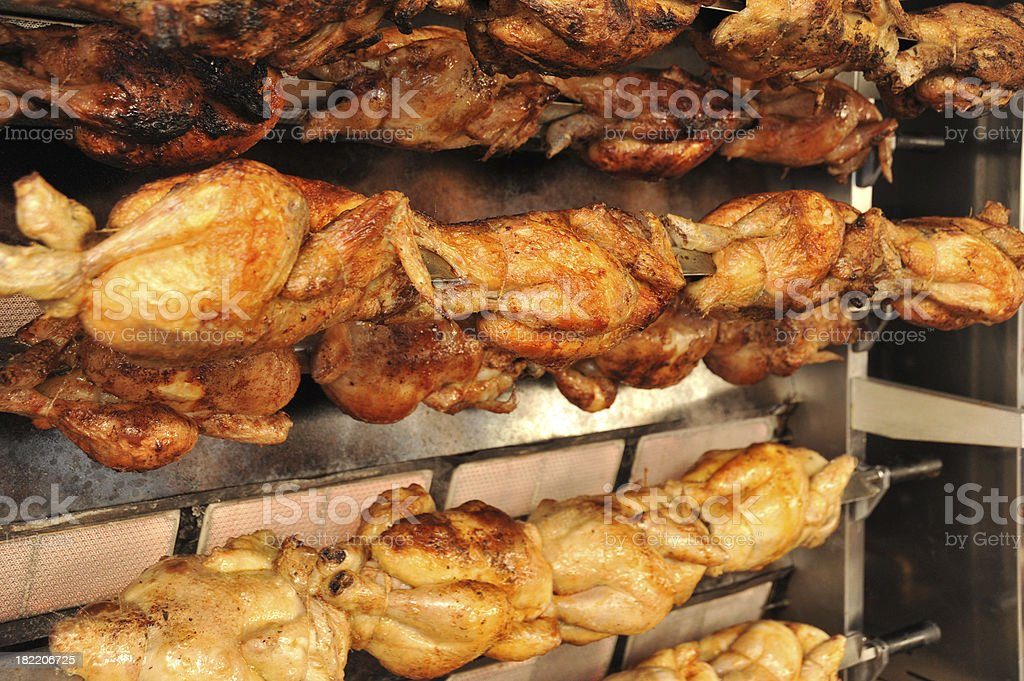 Rows of chickens cooking on a commercial rotisserie royalty-free stock photo