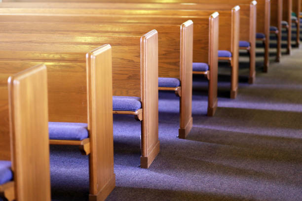 Rows of Church Pews in an Empty Church Sanctuary Window light is shing on rows of empty church pews in a Church Sanctuary without any people in it. church stock pictures, royalty-free photos & images