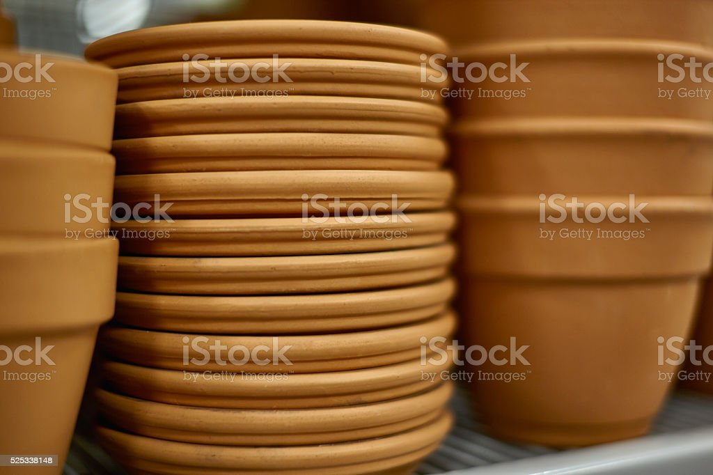 Rows of Clay Pots with Trays on Shelf stock photo