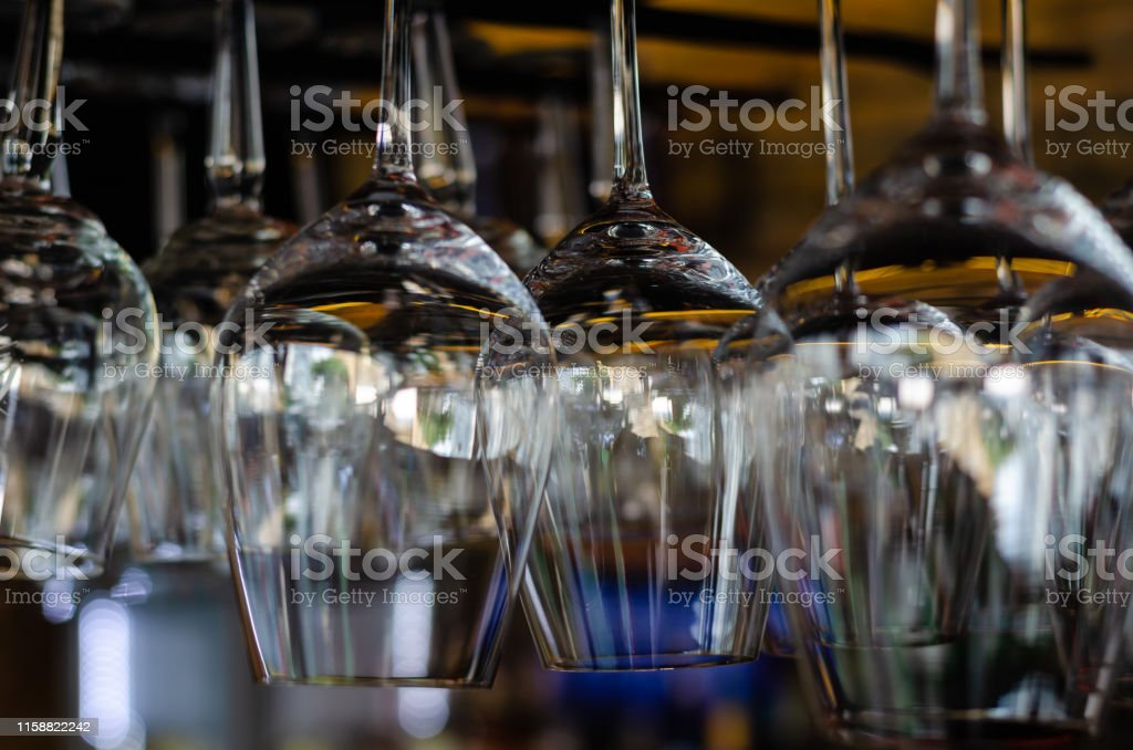 Rows of clean empty glasses above the bar counter. Interior of pub,...