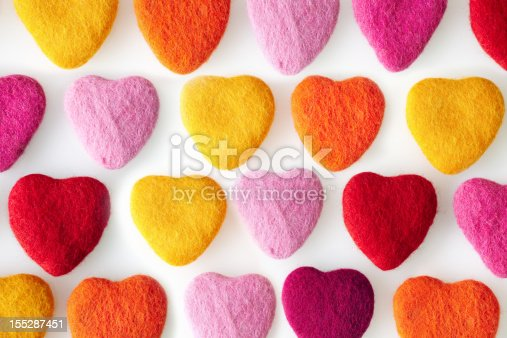 Rows of colorful felt shaped hearts made from wool felt on a white background