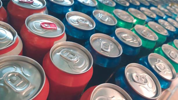 reihen von bunten metalldosen mit soda-drink im laden - alkoholfreies getränk stock-fotos und bilder