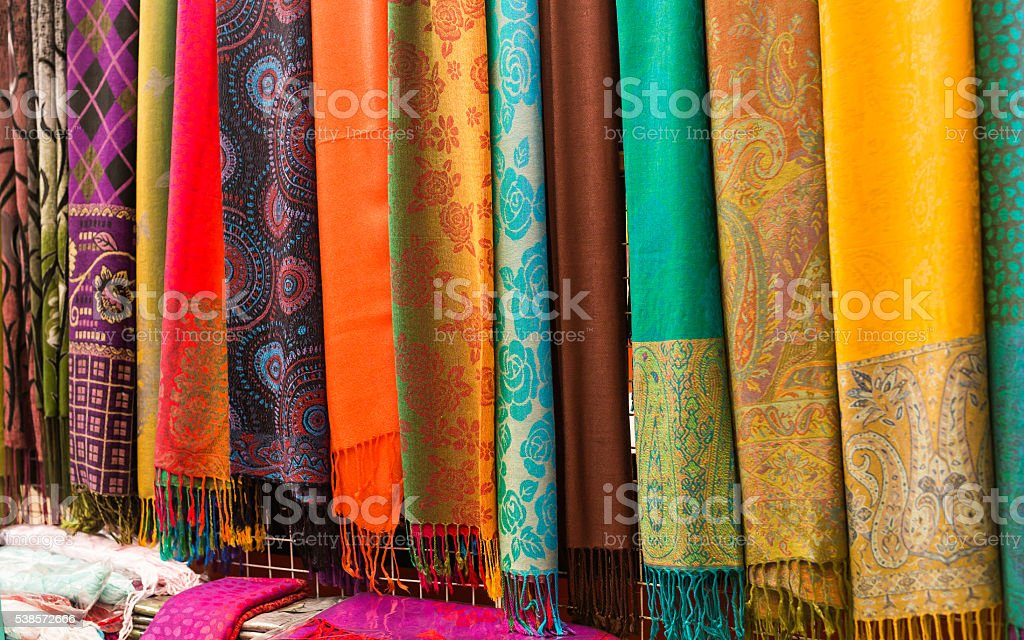 Rows of colourful silk scarfs hanging at a market stall stock photo