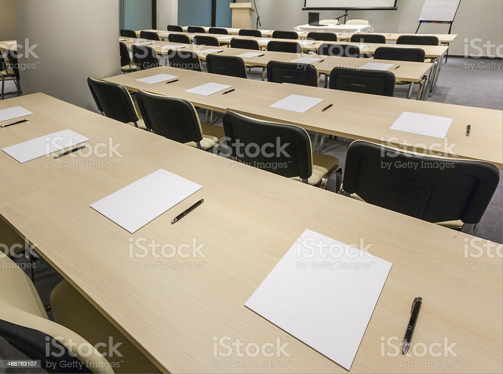 Rows of desks with pen and paper in classroom stock photo