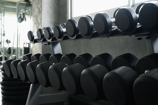 Rows of dumbbells in the gym background for banner presentation. Themes about exercise for good health.