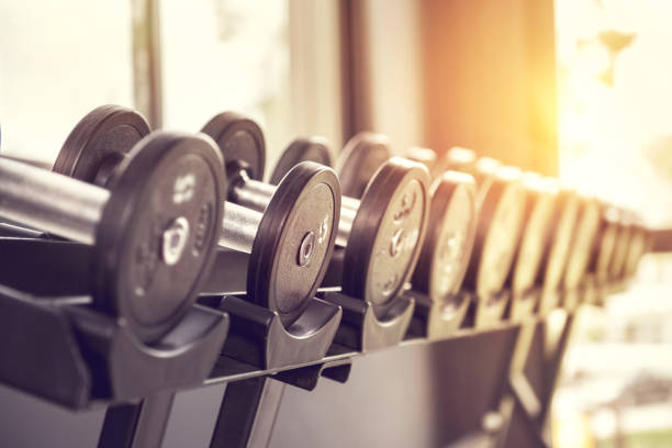rows of dumbbells in the gym with sunlight. - weights stock photos and pictures