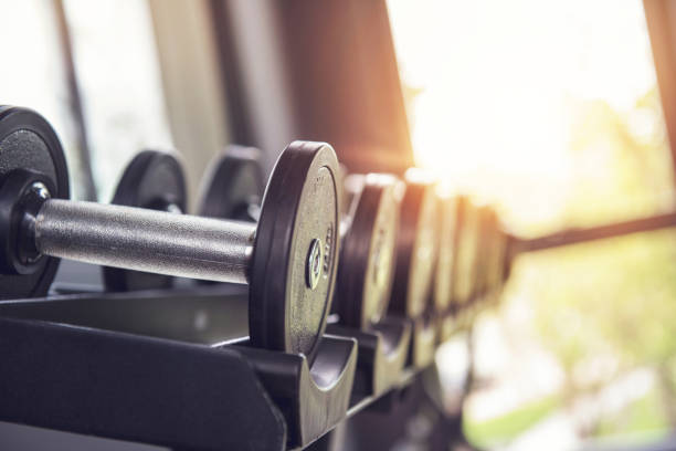 Rows of dumbbells in the gym with sunlight. stock photo