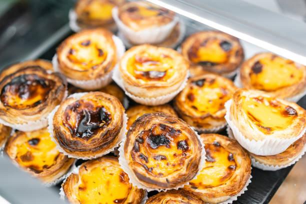 reihen von ei-torte, traditionelle portugiesische süßspeise, pasteis de nata, pudding kuchen. cafe auf den straßen von lissabon, portugal - portugiesische desserts stock-fotos und bilder