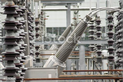 A series of smaller electrical insulators frame a large insulator at a electrical substation.  Electrical power conversion for residential and industrial use.  Similar photos: