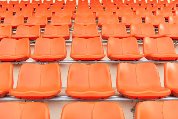Rows of empty orange plastic grandstand seats at . stock photo
