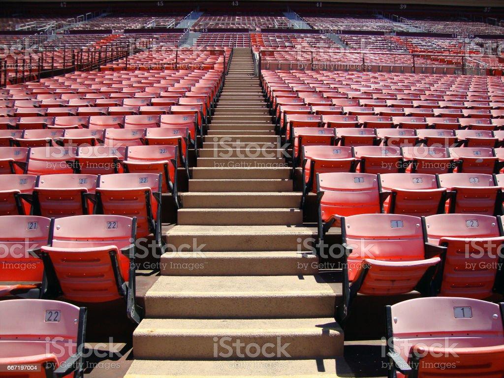 Rows of empty orange stadium seats going upward stock photo