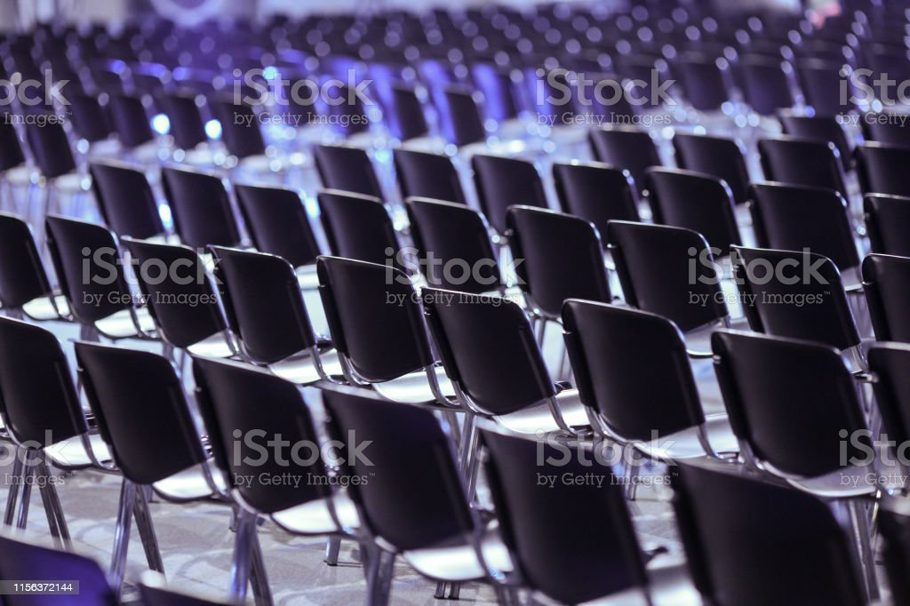 Rows of empty plastic seats in an empty conference room - no people.