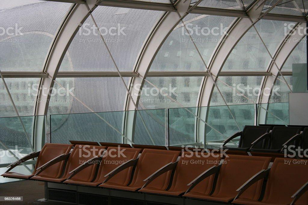 File di posti vuoti contro la parete in vetro a giorno di pioggia foto stock royalty-free