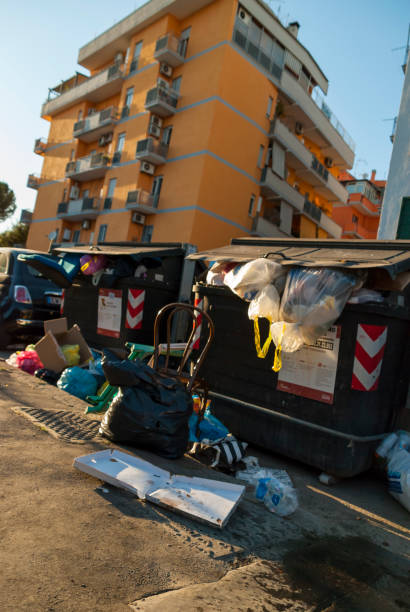 Rows of garbage containers with rubbish and a broken chair on the street - foto stock