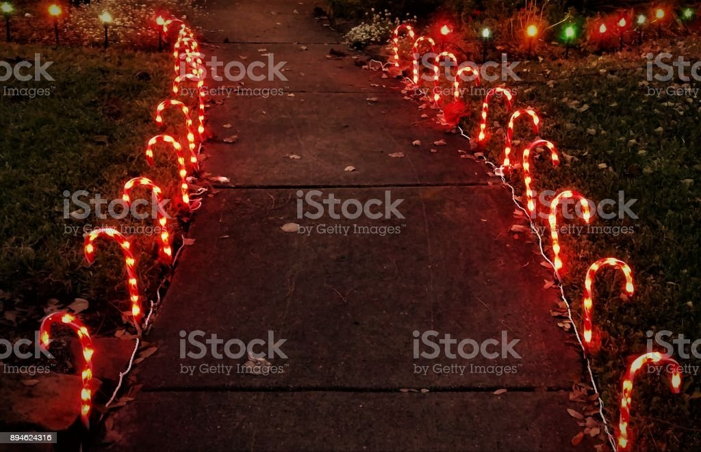 Rows of Glowing Candy Canes along a Walkway -- Night stock photo