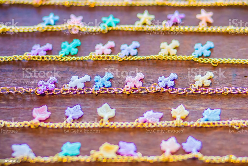 Rows of golden bracelet chain with cute pendants for sale in the jewelry shop. Golden handmade necklace chains set with colorful pendants royalty-free stock photo