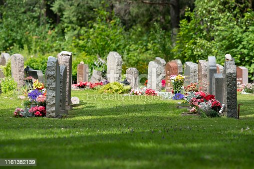 Sun shining on rows of gravestones with colorful flowers on a beautiful and well cared cemetery