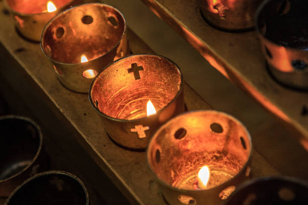 Rows of lit candles in church stock photo