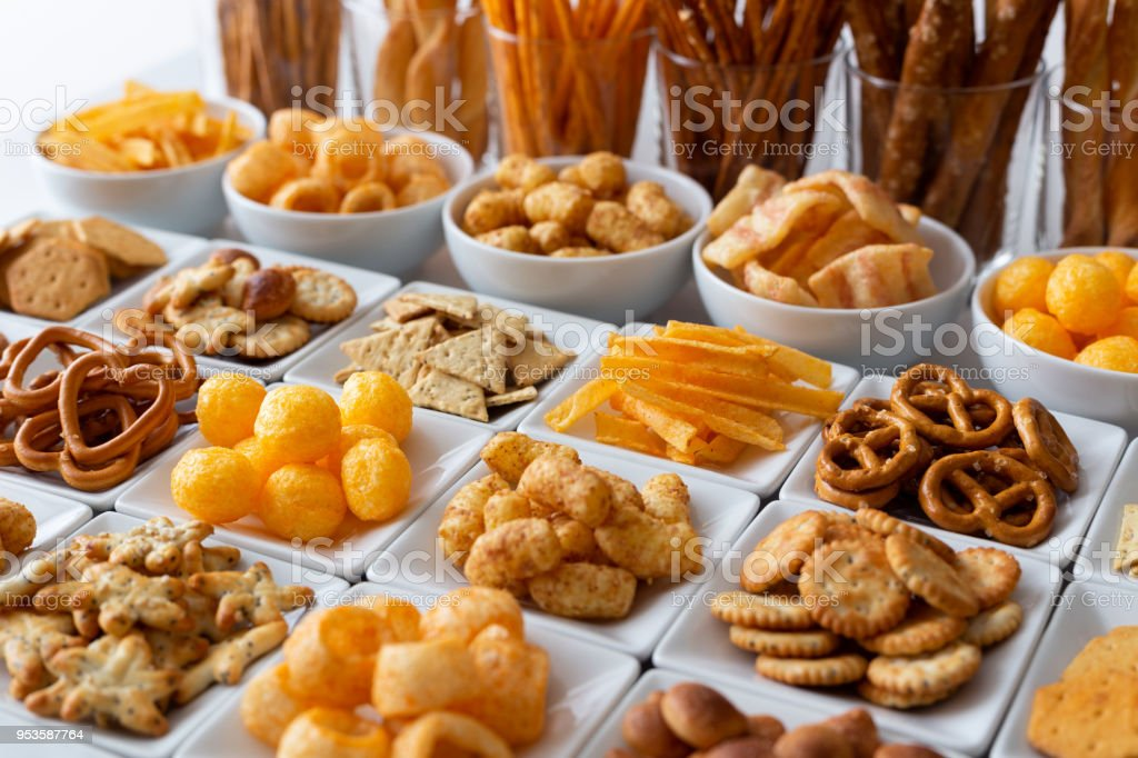 Rows of many types of savory snacks in white ceramic dishes. stock photo