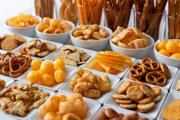 linhas de muitos tipos de snacks salgados em pratos de cerâmicos brancos. - comida salgada - fotografias e filmes do acervo