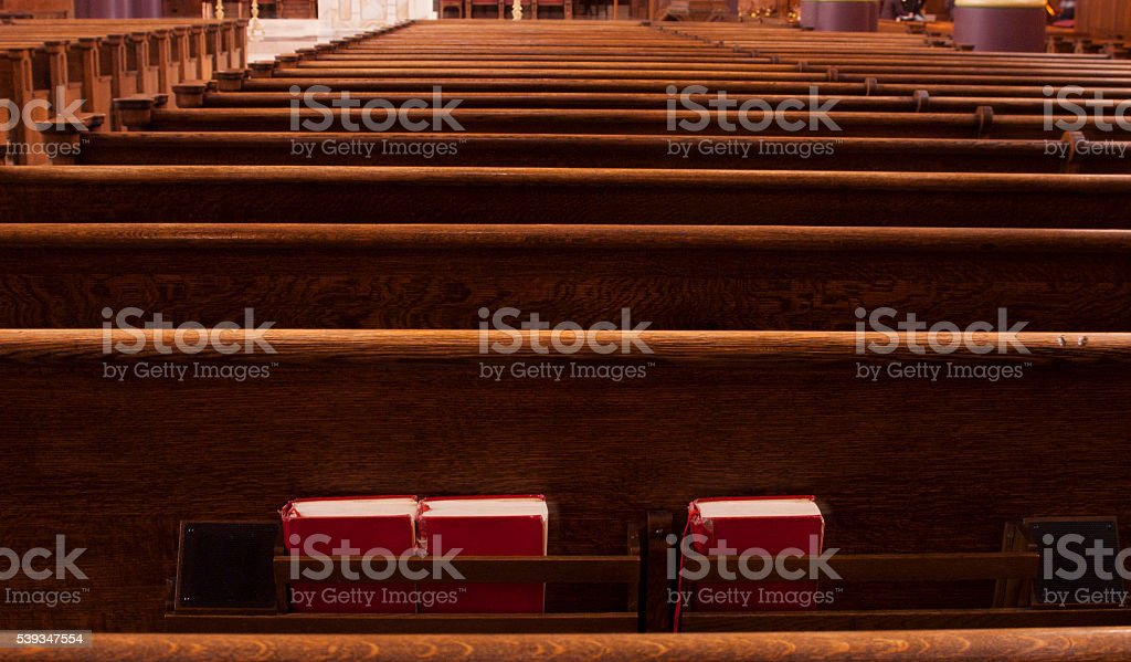 Rows of pews in Catholic church with three red Bibles stock photo