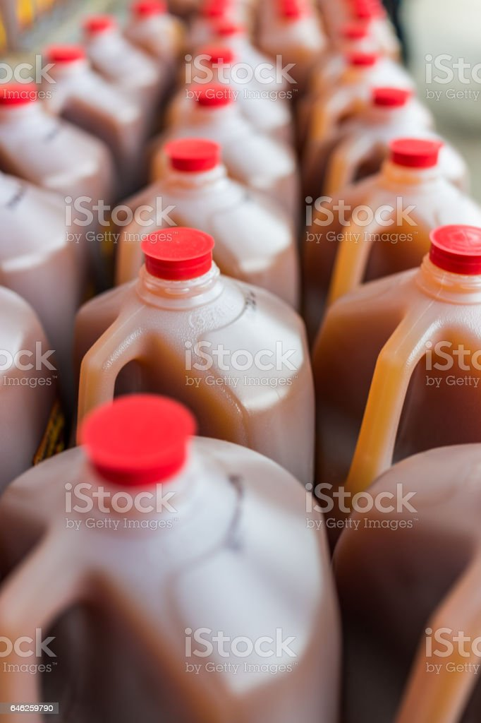 Rows of plastic gallon jars filled with apple cider stock photo