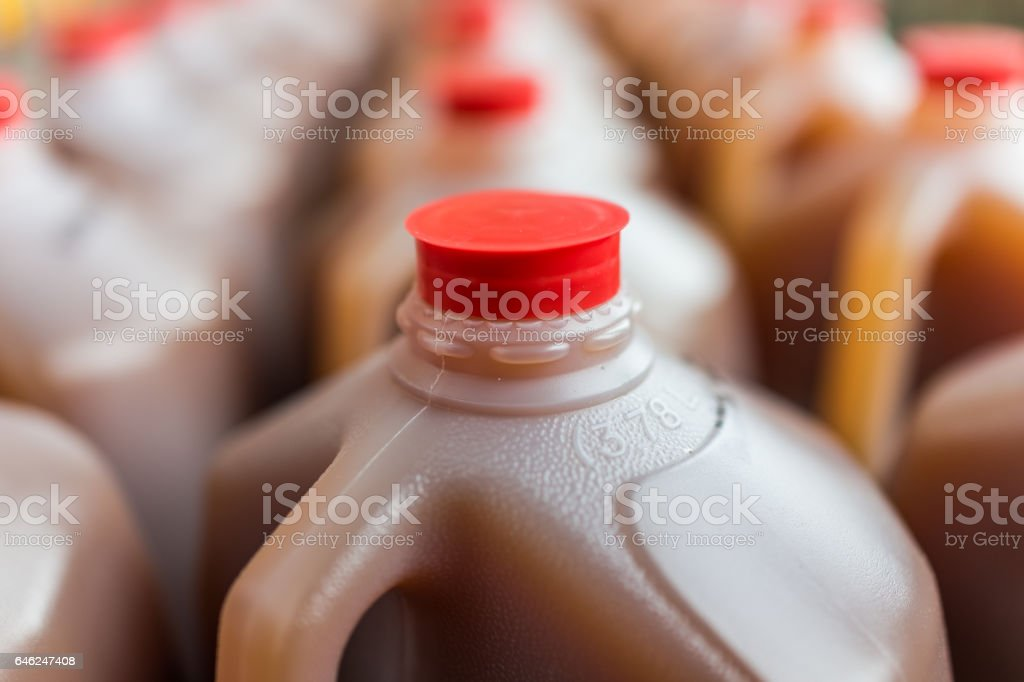 Rows of plastic gallon jars on display filled with cider stock photo