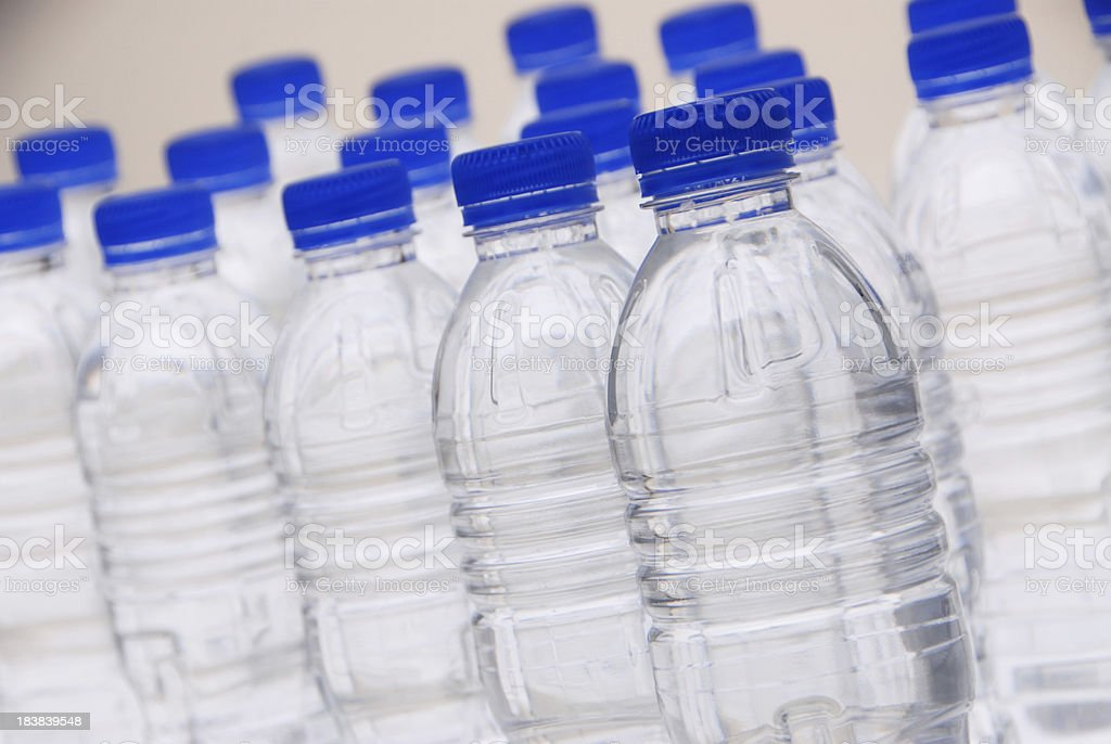 Rows of plastic water bottles with blue caps stock photo