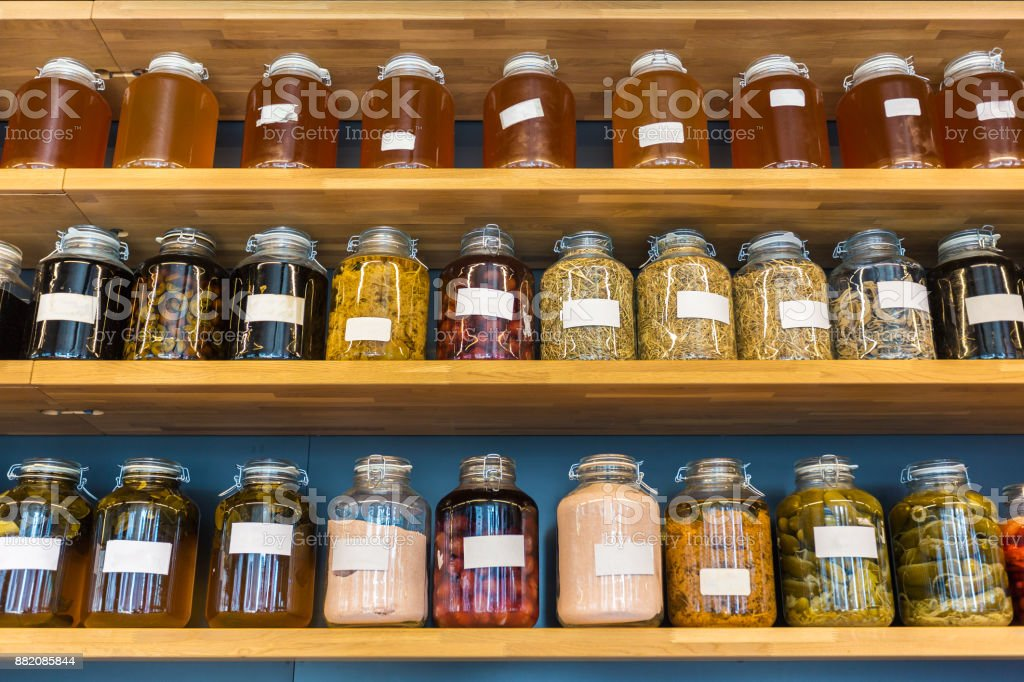 rows of preserved food in glass jars on wooded shelves, good for food...