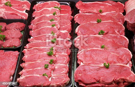 istock Rows of raw beef steaks with garnish 450497997