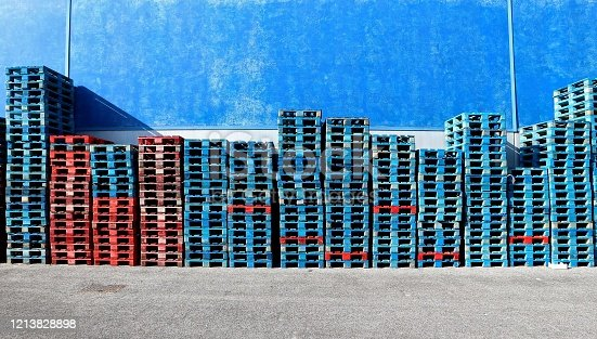 Rows of red and blue painted wooden pallets stacked against a blue wall. Asphalt road ahead. Background for copy space.