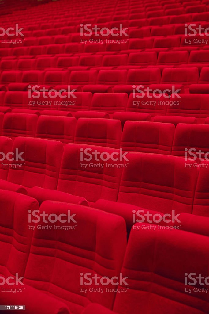 Rows of red arm-chairs in empty hall stock photo