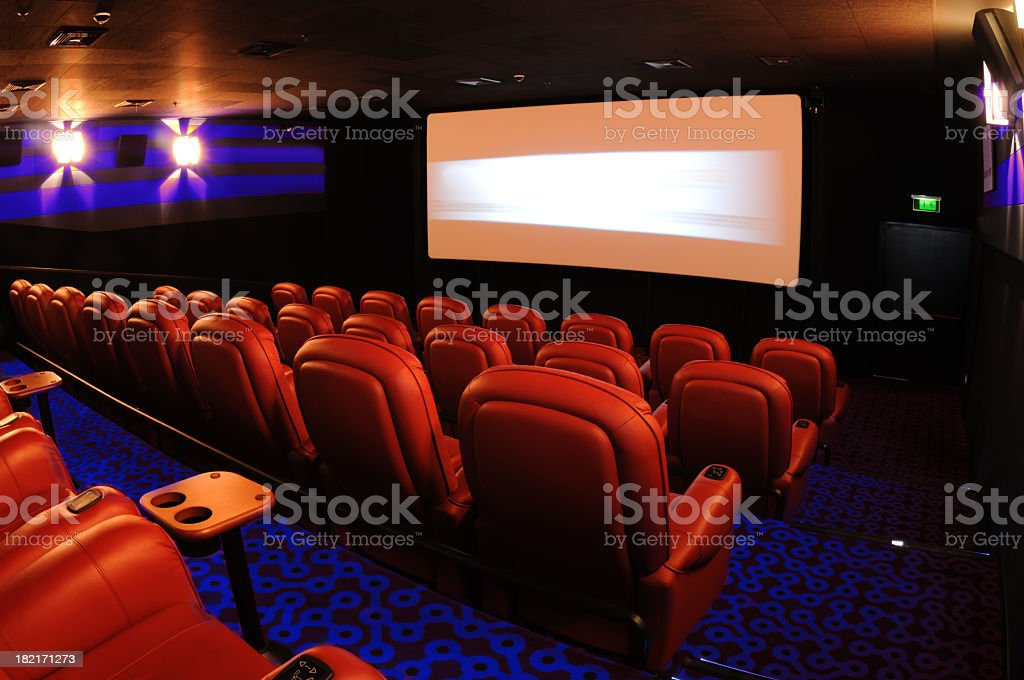 Rows of red movie theater seats facing the movie screen royalty-free stock photo