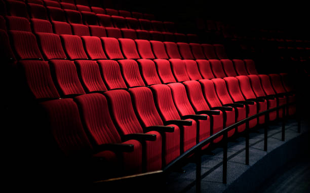 Rows of red seats in a theater stock photo