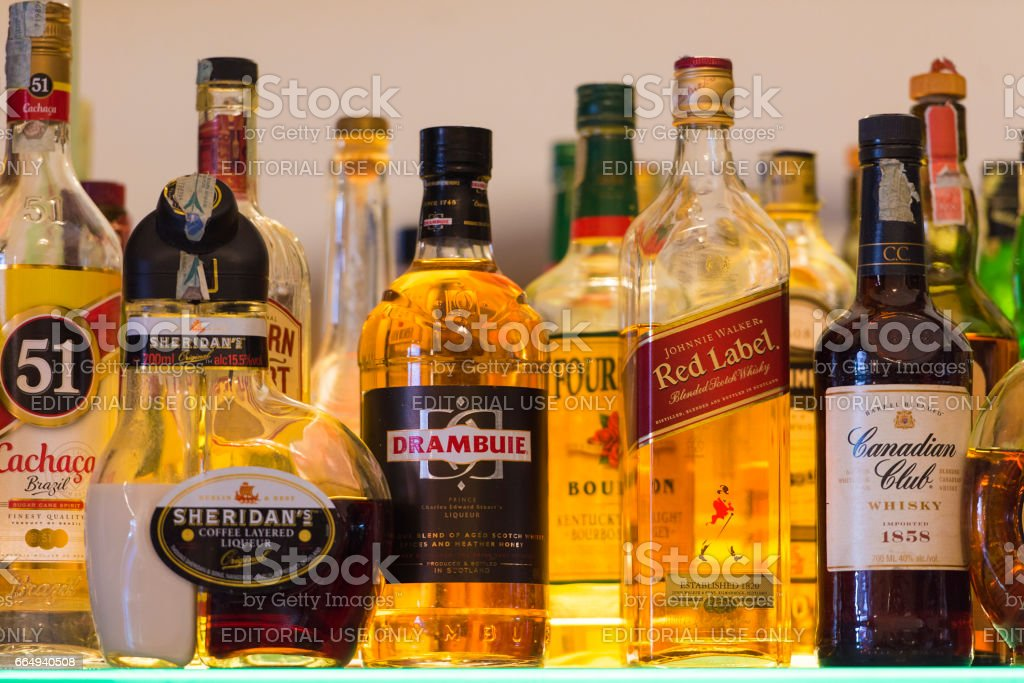Rows of several types of bottles with alcoholic beverages at a bar in Naples, stock photo