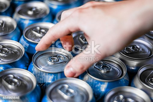 A shot from above of a number of blue new and sealed soda cans arranged in rows and a hand reaching and touching on of the cans.