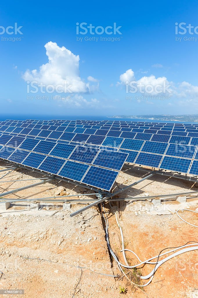 Rows of solar panels near sea with blue sky stock photo