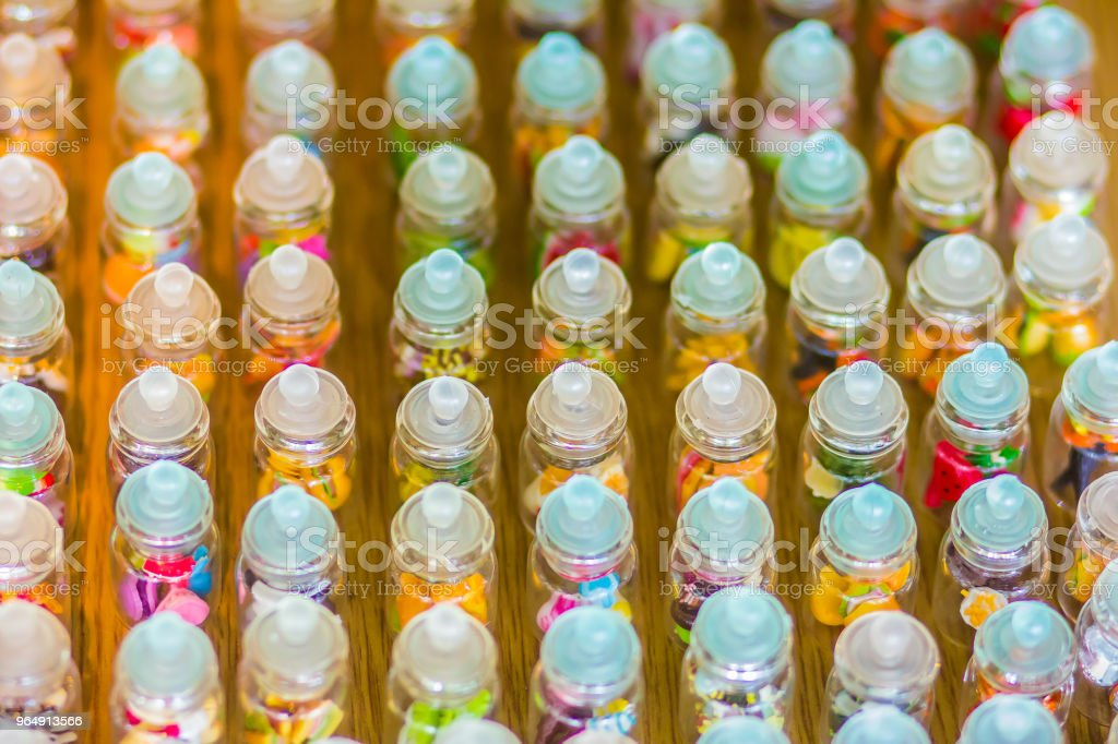 Rows of tiny glass jars with colorful lids for sale at the street market in Bangkok royalty-free stock photo